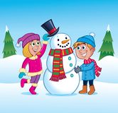 Bambini che fanno un pupazzo di neve nella neve immagine stock