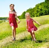 Bambini che funzionano attraverso l'erba verde esterna. Fotografia Stock