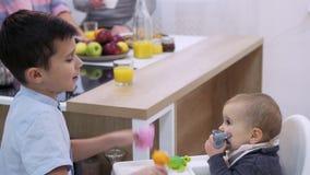 Bambini che giocano accanto al tavolo da pranzo video d archivio