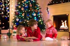 Bambini che giocano al camino sulla notte di Natale Immagini Stock
