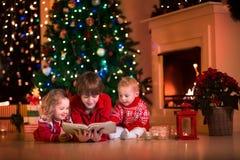 Bambini che giocano al camino sulla notte di Natale Fotografie Stock Libere da Diritti