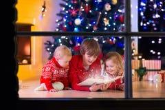 Bambini che giocano al camino sulla notte di Natale Immagine Stock