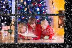 Bambini che giocano al camino sulla notte di Natale Fotografie Stock