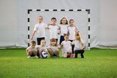 Bambini che giocano a calcio all'interno Squadra di football americano dei bambini immagini stock