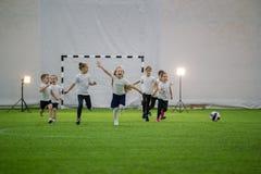 Bambini che giocano a calcio all'interno Squadra di football americano emozionante dei bambini che corre sul campo immagine stock libera da diritti