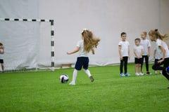 Bambini che giocano a calcio nell'arena dell'interno di calcio fotografia stock