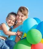 Bambini che giocano con gli aerostati alla spiaggia Immagine Stock