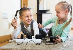 Bambini che giocano con gli incavi e l'elettricità all'interno Immagine Stock