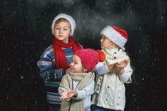 Bambini che giocano con i fiocchi di neve su un fondo scuro immagine stock libera da diritti