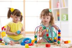 Bambini che giocano con i giocattoli nell'asilo Fotografie Stock Libere da Diritti