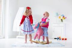 Bambini che giocano con il cavallo di oscillazione Fotografie Stock