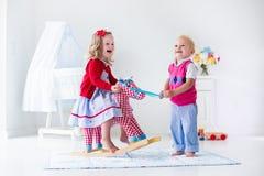 Bambini che giocano con il cavallo di oscillazione Fotografie Stock Libere da Diritti