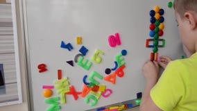 Bambini che giocano con il tavolo da disegno e l'alfabeto magnetici video d archivio