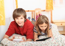Bambini che giocano con la compressa e lo smartphone Fotografie Stock