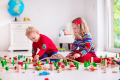 Bambini che giocano con la ferrovia ed il treno del giocattolo fotografie stock libere da diritti