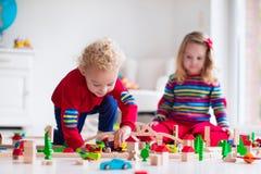Bambini che giocano con la ferrovia ed il treno del giocattolo Fotografia Stock