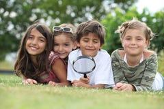 Bambini che giocano con la lente d'ingrandimento Fotografia Stock