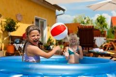 Bambini che giocano con la sfera nel raggruppamento di acqua Immagini Stock