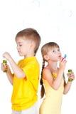 Bambini che giocano con le bolle isolate su bianco Immagine Stock