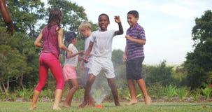 Bambini che giocano con lo spruzzatore del giardino archivi video