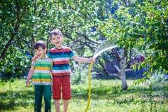 Bambini che giocano con lo spruzzatore del giardino Il bambino in età prescolare scherza il funzionamento e Immagine Stock