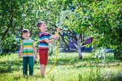 Bambini che giocano con lo spruzzatore del giardino Il bambino in età prescolare scherza il funzionamento e Fotografia Stock