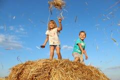 Bambini che giocano con un fieno, una paglia di frumento su un mucchio di fieno Immagine Stock