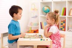 Bambini che giocano gioco da tavolo nella loro stanza Immagine Stock Libera da Diritti
