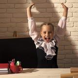Bambini che giocano - gioco felice La ragazza si siede allo scrittorio con cancelleria variopinta ed i libri Fotografie Stock