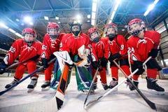 Bambini che giocano hockey su ghiaccio sulla pista di pattinaggio fotografia stock libera da diritti