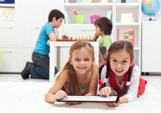 Bambini che giocano i giochi da tavolo classici ed il gioco di computer moderno della compressa Immagine Stock