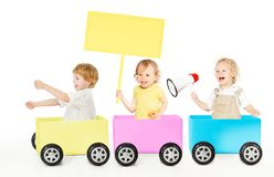 Bambini che giocano il giocattolo di pubblicità del treno Bambini con il bordo ed il megafono in bianco degli annunci su bianco immagine stock