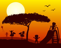 Bambini che giocano le siluette al tramonto Fotografia Stock