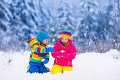 Bambini che giocano nel parco nevoso di inverno Immagine Stock