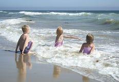 Bambini che giocano nell'acqua alla spiaggia fotografia stock libera da diritti