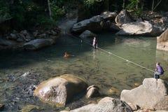 Bambini che giocano nell'acqua con il banco di pesci immagine stock libera da diritti