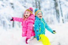 Bambini che giocano nella neve Gioco di bambini all'aperto in precipitazioni nevose di inverno fotografie stock