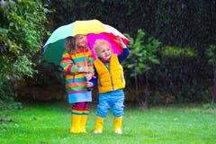 Bambini che giocano nella pioggia sotto l'ombrello variopinto Fotografia Stock Libera da Diritti