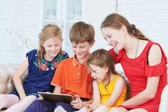 Bambini che giocano sul computer della compressa immagini stock