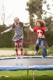 Bambini che giocano sul trampolino Fotografie Stock Libere da Diritti