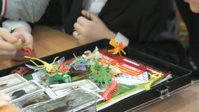 Bambini che giocano sulla tavola con i ragni di gomma stock footage