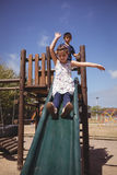 Bambini che giocano sullo scorrevole immagine stock