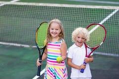 Bambini che giocano a tennis sulla corte all'aperto fotografie stock libere da diritti