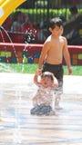 Bambini che giocano in una zona di impatto dell'onda alla sosta locale fotografie stock libere da diritti