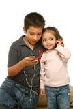 Bambini che godono di un giocatore mp4 Immagine Stock