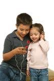 Bambini che godono di un giocatore mp4 Fotografia Stock