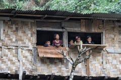 Bambini che guardano dalla finestra della capanna Immagini Stock Libere da Diritti