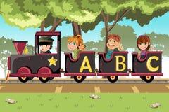 Bambini che guidano il treno di alfabeto Fotografia Stock