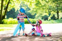 Bambini che guidano pattino nel parco di estate fotografia stock libera da diritti