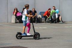 Bambini che guidano un motorino e una gente elettrici che riposano sul benche immagine stock
